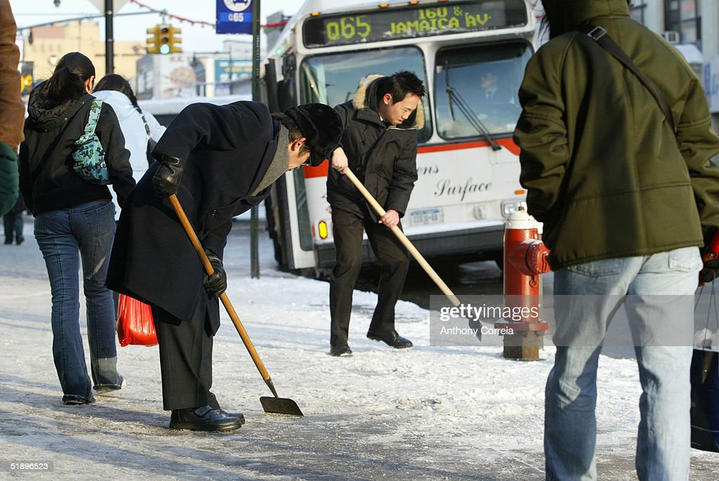 Men clean ice and snow off a sidewalk along Main Street December 27 2004 in the Flushing neighborhood of the Queens borough of New York City About...