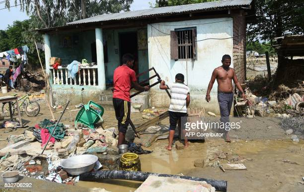 Men clean their house and belongings after the area was hit by flood in Itahari Sunsari district some 250 kms from Nepal's capital Kathmandu on...