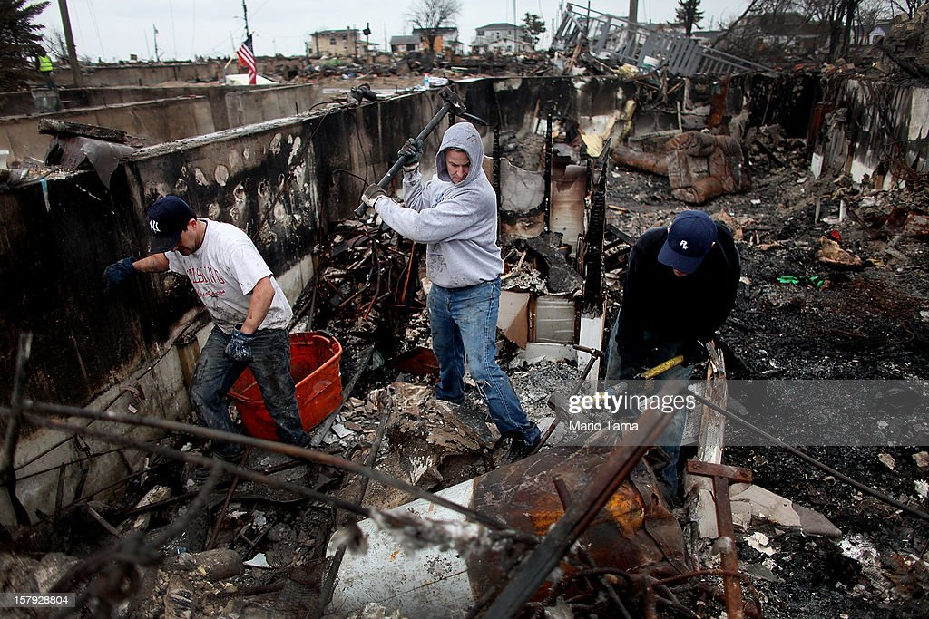 Men clear debris from the charred remains of a destroyed home in the hard hit Breezy Point neighborhood on December 7, 2012 in the Queens borough of New York City. Breezy Point, home to many New York City firefighters and police, lost 111 homes in a fast moving fire during Superstorm Sandy with many more homes severely damaged from flooding.