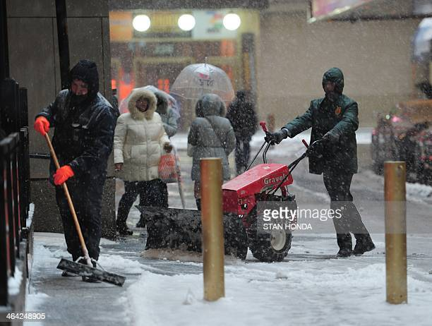 Men clear snow on a sidewalk between West 45th and West 44th Streets as snow falls January 21 2014 in New York In New York a storm alert was issue...
