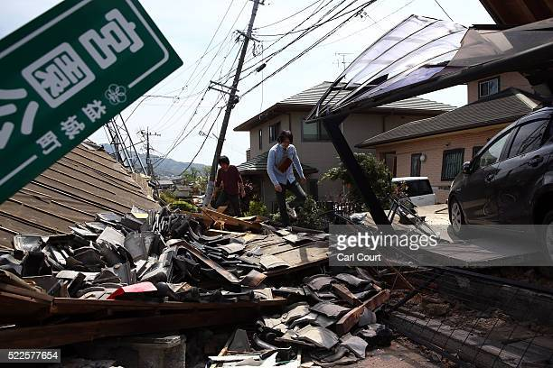 Men climb over the rubble of a collapsed house following an earthquake on April 20 2016 in Mashiki near Kumamoto Japan As of April 20 48 people were...