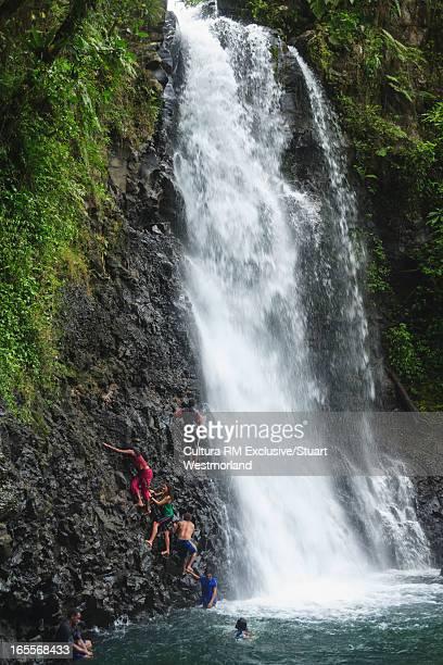 Men climbing rocky cliff by waterfall