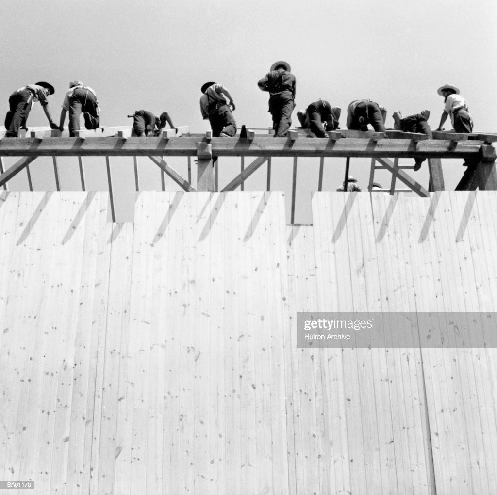 Men constructing barn, low-angle view (B&W) : Stock Photo
