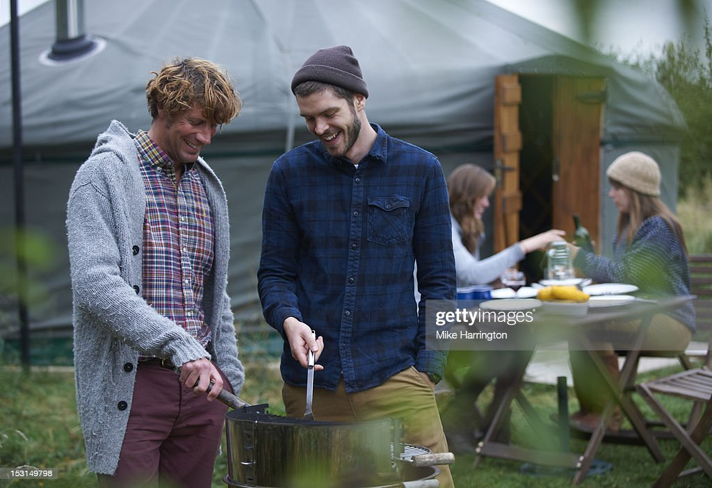 Men conversing over barbecue on glamping holiday. : Stock Photo