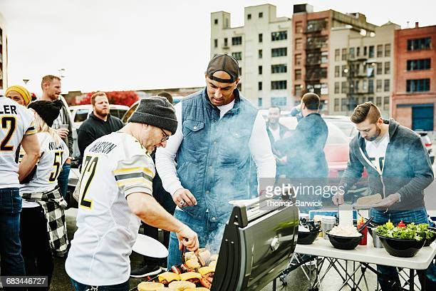 Men cooking at barbecue during tailgating party