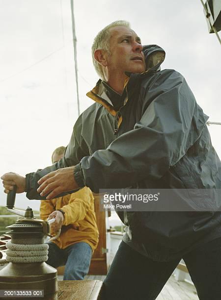 Men cranking rope on sailboat