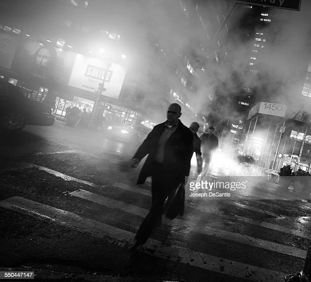 Men crossing the street near Times Square in heavy steam and fog Manhattan New York City New York