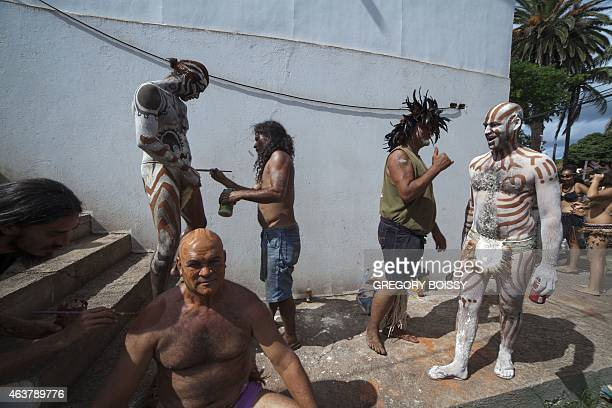 Men decorated their bodies as they prepare for the parade on February 12 2015 in Hanga Roa on Chile's Easter Island as people take part in the two...