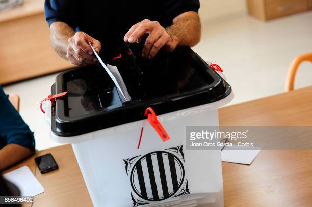 A men deposited a ballot in the ballot boxe during the Catalonia independence referendum declared ilegal by the Spanish government on October 1 2017...