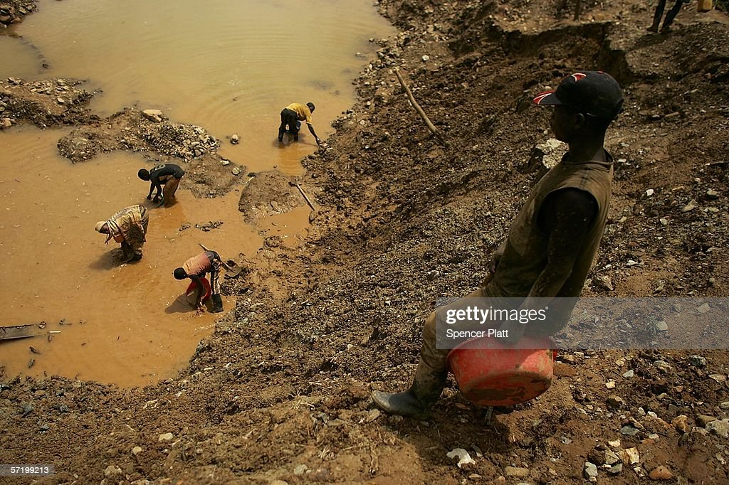 A Men dig through dirt and mud while looking for gold at an abandoned industrial mine March 28, 2006 in Mongbwalu, Congo. Thousands of Congolese scrape together meager livings from mining. Gold and other mineral deposits, which are numerous in the volatile north-east of the country, have become a catalyst to much of the conflict in Congo. The Democratic Republic of Congo (DRC), a country that loses an estimated 1,400 people per day due to war since 1998, is struggling to hold Presidential elections this summer. The volatile east of the country, which is situated hundreds of miles from the capital Kinshasa, has been the focal point of continued violence. Numerous militias and warlords have vied for control of the mineral rich eastern Congo for decades, creating instability and continued bloodshed.