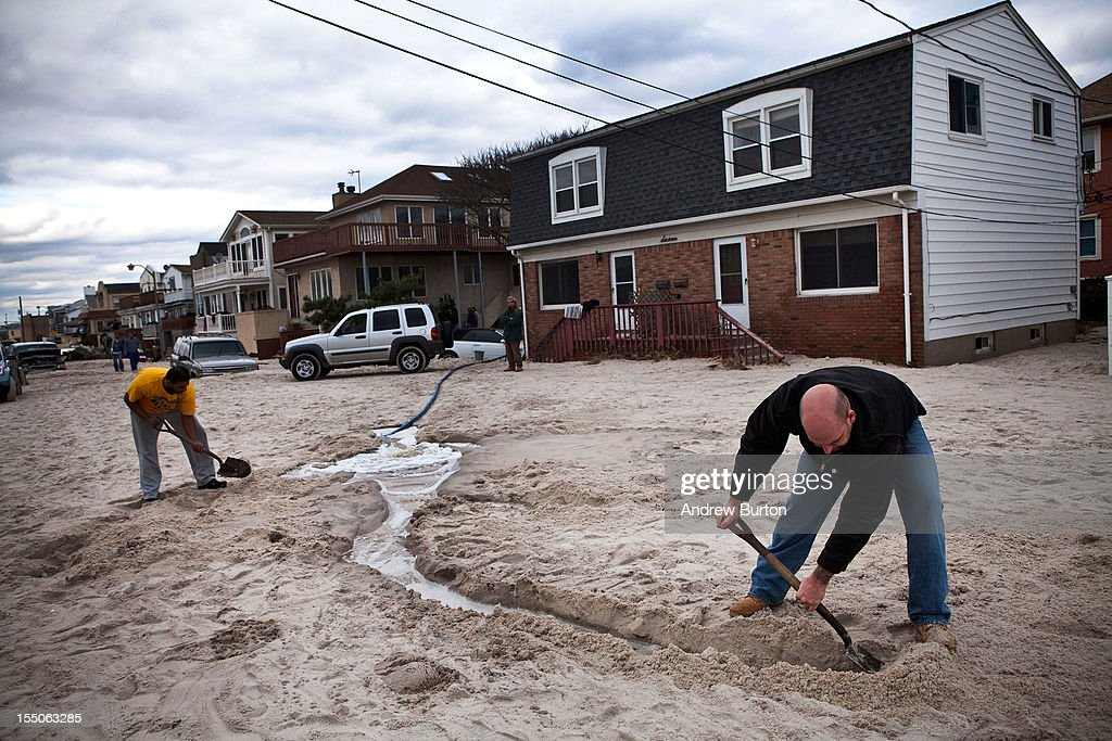 Men dig trenches for water being pumped out of flooded basements caused by Hurricane Sandy on October 31 2012 in Long Beach New YorkThe storm has...