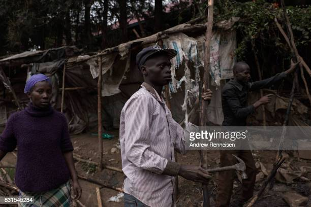Men dismantle a roadside stand that was burnt the during unrest the day prior in the Mathare North neighborhood on August 14 2017 in Nairobi Kenya...