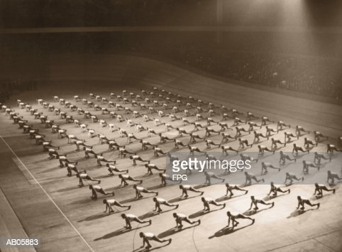 Men doing gymnastics in unison in hall, elevated view (B&W sepia tone) : Stock Photo