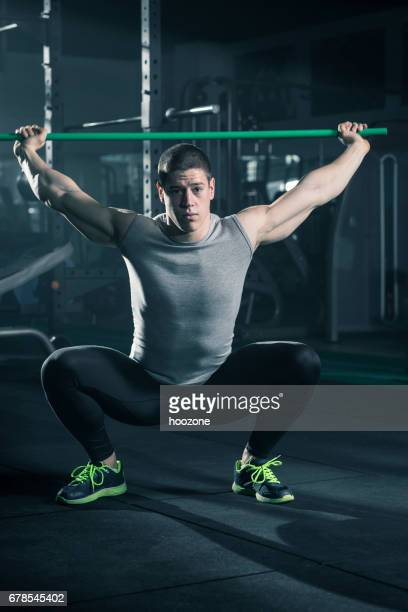 Men doing squats with bar at gym