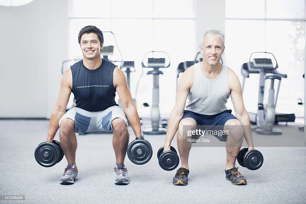 Men doing squats with dumbbells in gymnasium : Stock Photo
