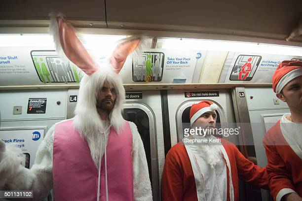 Men dressed as a Santa ride the subway with a man dressed as the Easter Bunny during the annual SantaCon pub crawl December 12 2015 in the Brooklyn...