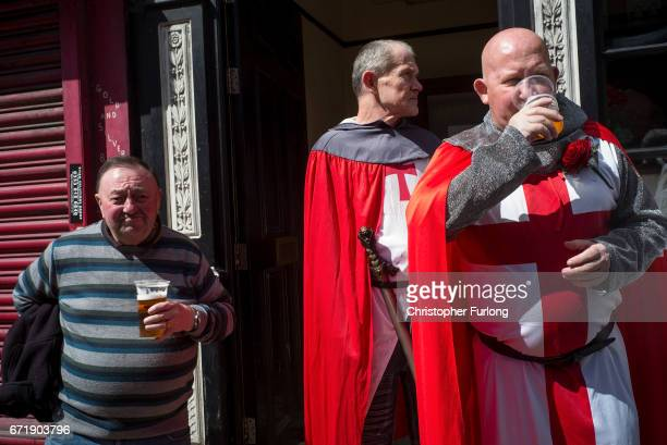 Men dressed as knights enjoy a pint of beer outside a pub as they watch the Manchester St George's Day parade through the streets on April 23 2017 in...
