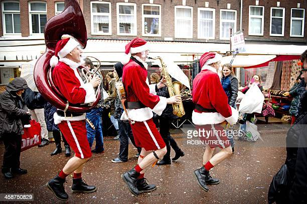 Men dressed as Santa Claus play music at the Albert Cuypmarkt in Amsterdam during the last weekend before Christmas in the Netherlands on December 21...