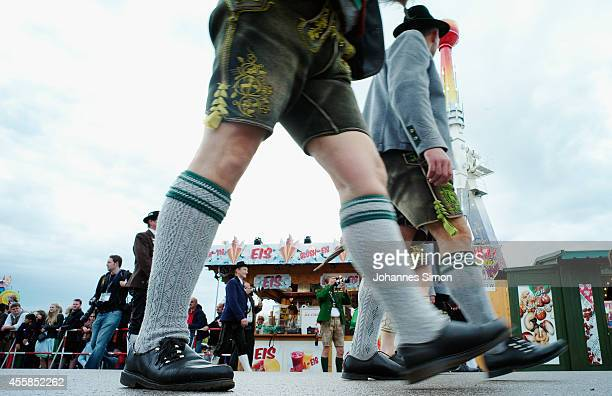 Men dressed in Lederhosen and other traditional Bavarian folk dress march in the Parade of Costumes and Riflemen on the second day of the 2014...