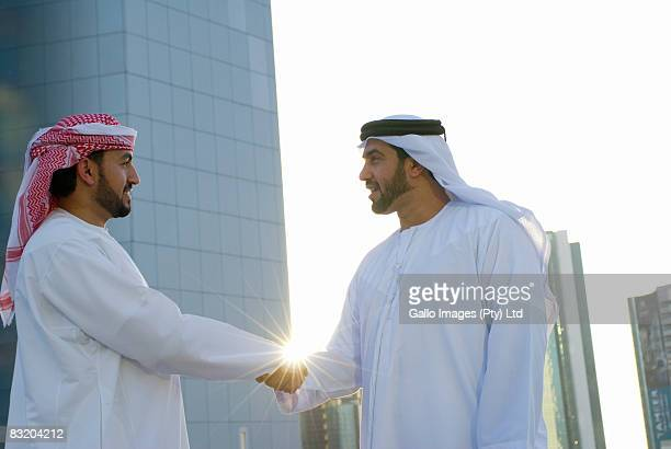Men dressed in traditionally Middle Eastern attire shaking hands, Dubai cityscape in background, UAE