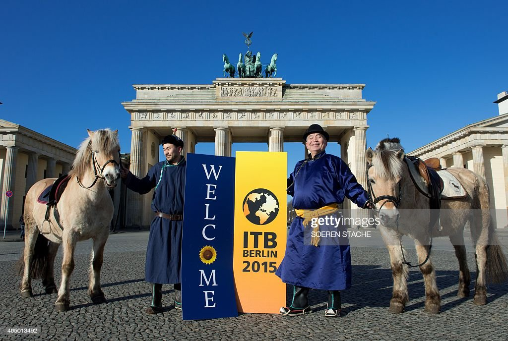 Men dressed up as as Mongolian steppe horsemen pose on March 3 2015 in front of the Brandenburg Gate with a banner ' Welcome to ITB in Berlin The...