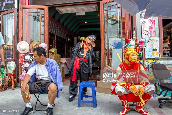 Men dressed up as Sun Wukong and Pigsy rest in a tourist souvenir shop They make living by taking photos with tourists In the midst of a stock market...