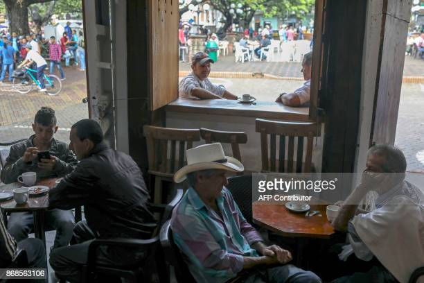 Men drink coffee at a Cafe in Ciudad Bolivar Antioquia department Colombia on October 22 2017 October is the peak of the coffee harvest season in the...