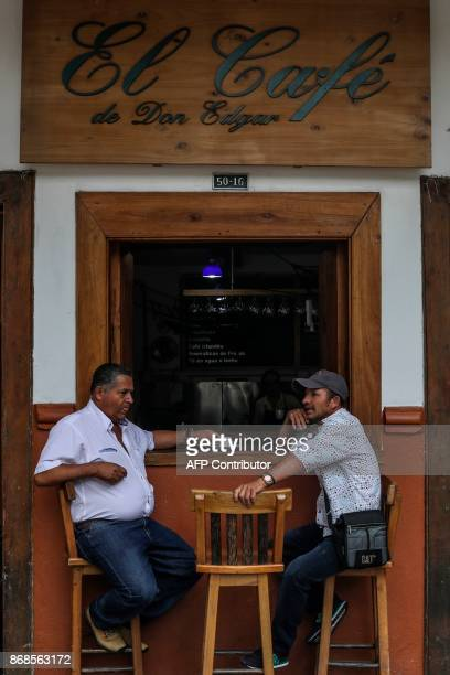 Men drink coffee at a Coffee Shop in Ciudad Bolivar Antioquias Department on October 22 2017 October is the peak of the high season coffee harvest in...