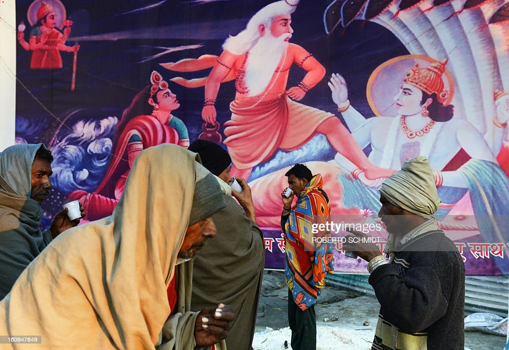 Men drink hot tea near a painting depicting Hindu gods in confrontation at the entrance of one of hundreds of camps set up by different Hindu religious factions at the Maha Kumbh Mela festival in Allahabad on February 8, 2013. The Kumbh Mela in the town of Allahabad will see up to 100 million worshippers gather over 55 days to take a ritual bath in the holy waters, believed to cleanse sins and bestow blessings. AFP PHOTO/ ROBERTO SCHMIDT