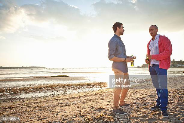 Men drinking beer and chatting on beach