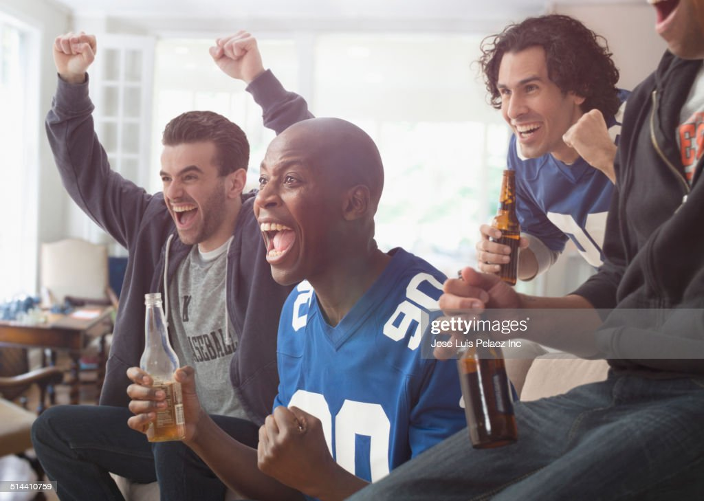 Men drinking beer and cheering at game on television
