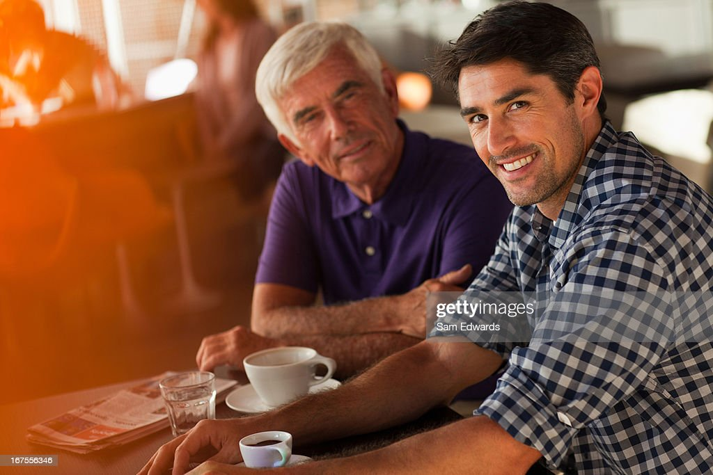 Men drinking coffee together in cafe : Stock Photo