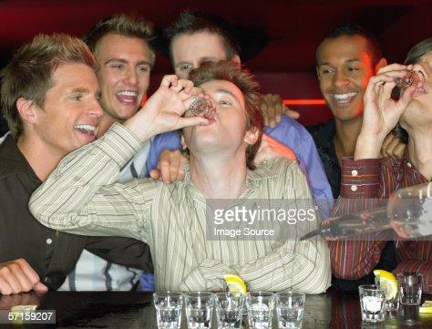 Men drinking shots at a bar