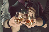 Three men drinking whiskey. Close up of glasses and hands. Dark tone.