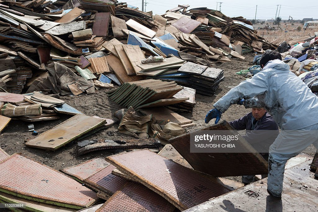 Men dump saturated tatami mats at a temporary dumping ground following the tsunami in Higashimatsushima, Miyagi prefecture on March 31, 2011. The number of confirmed dead and people listed as missing from the earthquake and tsunami that devastated Japan's northeast coast topped 28,000 on March 28. AFP PHOTO / YASUYOSHI CHIBA