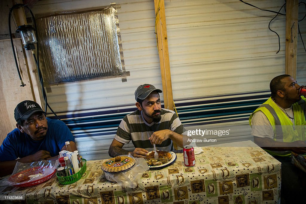 Men eat lunch in a make-shift restaurant, constructed of plywood and two-by-fours and attached to an RV, on July 23, 2013 outside Watford City, North Dakota. North Dakota has been experiencing an oil boom in recent years, due in part to new drilling techniques including hydraulic fracturing and horizontal drilling. In April 2013, The United States Geological Survey released a new study estimating the Bakken formation and surrounding oil fields could yield up to 7.4 billion barrels of oil, doubling their estimate of 2008, which was stated at 3.65 billion barrels of oil.