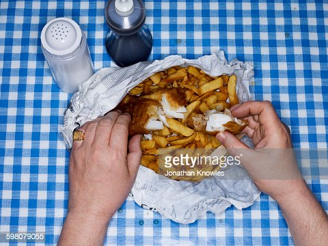 Men eating fish and chips, overhead view