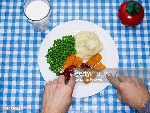 Men eating fish fingers, potatoes mash and peas