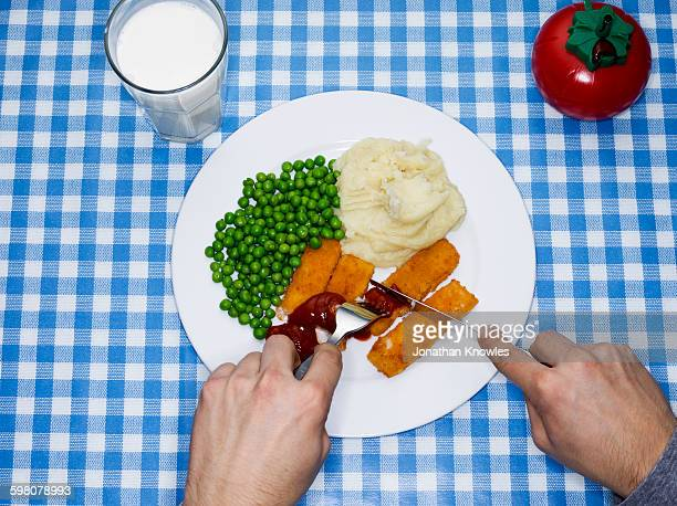 Men eating fish fingers, potatoes mash and peas
