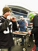 Men eating food at tailgate party