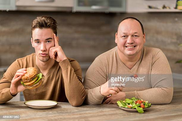Men eating in the kitchen and looking at camera.