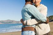 Men embracing on beach