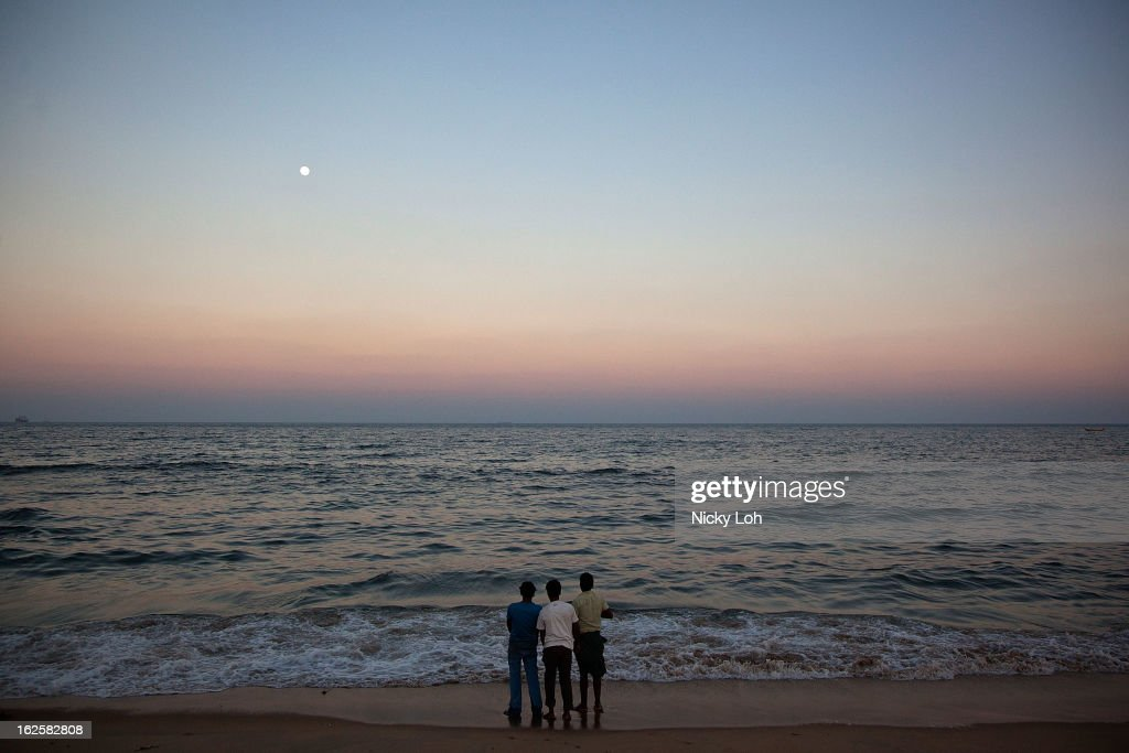 Men enjoy the view during sunset at the Marina Beach on February 24, 2013 in Chennai, India. Marina Beach is an urban beach along the Bay of Bengal, which is part of the Indian Ocean. The beach runs a distance of 13km (8.1 miles), making it the longest natural urban beach in the country and the world's second longest.