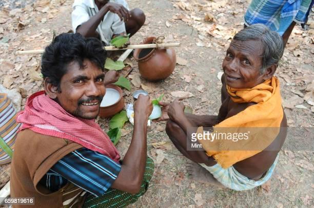 Men enjoying local drink called taadi in Bastar a maoist area on March 25 2010 in Chhattisgarh India