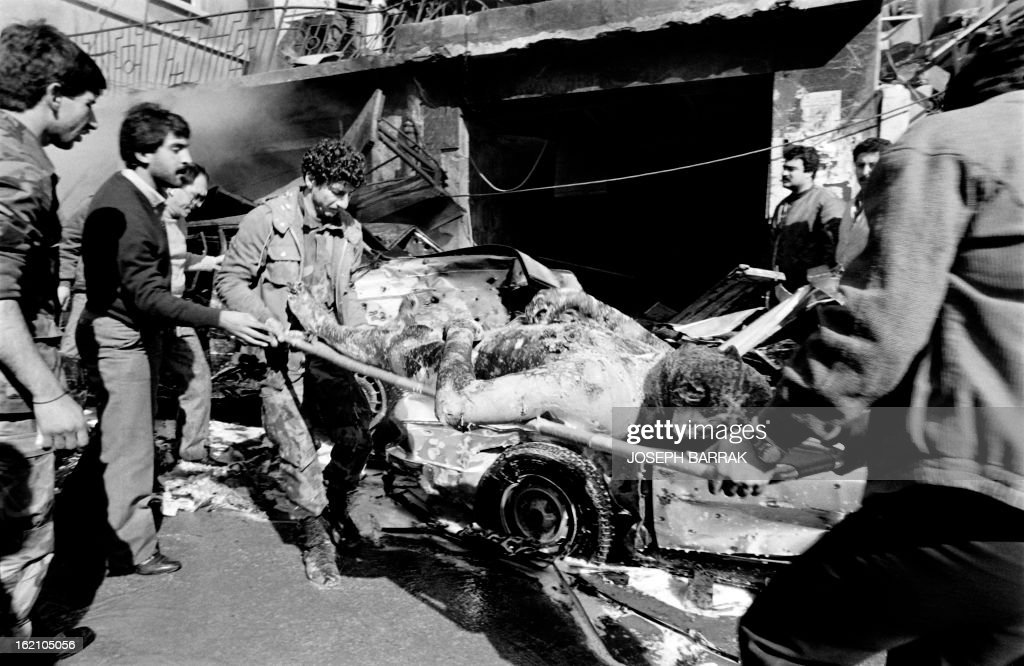 Men evacuate a victim after the explosion of a car bomb killed twenty people and one hundred wounded in a Christian suburb of Beirut, on January 21, 1986. AFP PHOTO JOSEPH BARRACK