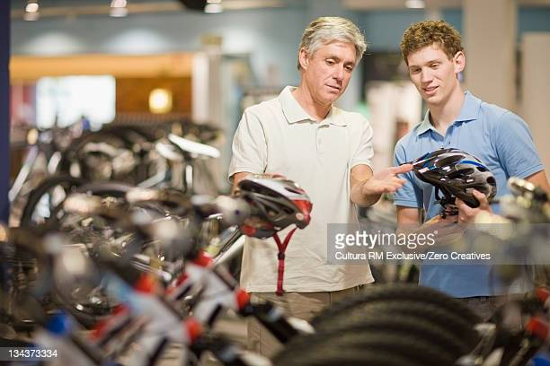 Men examining bicycle helmets in shop