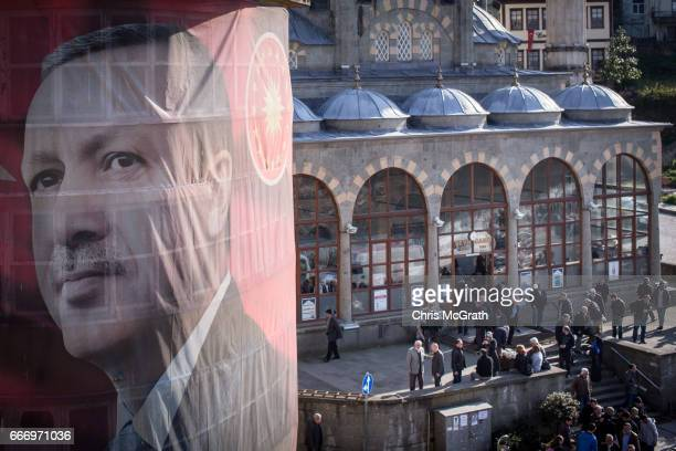 Men exit a mosque after afternoon prayer behind a banner showing the portrait of Turkish President Recep Tayyip Erdogan hanging from a building on...