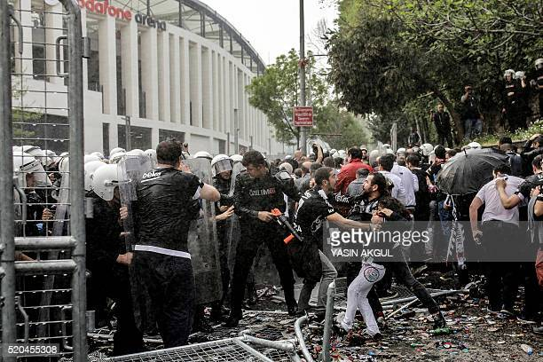 Men fight as Turkish antiriot police use tear gas and water cannon to disperse supporters around the stadium before the Turkish Spor Toto Super...