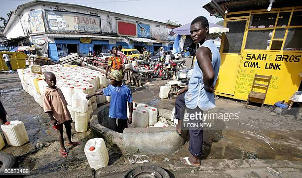 Men fill water drums from an underground water main near the Waterside Market in Monrovia on April 22 2008 United Nations SecretaryGeneral Ban Kimoon...