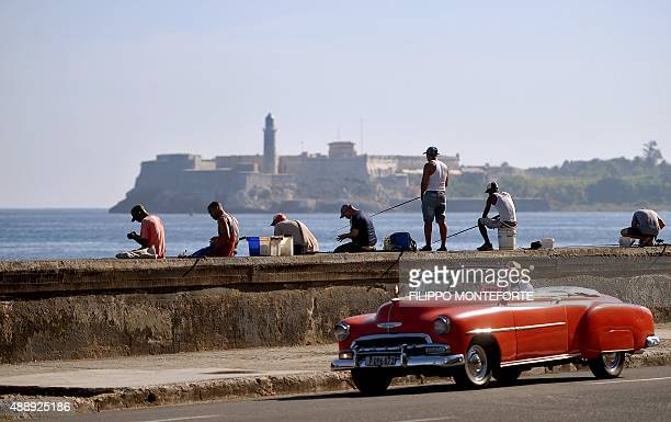 Men fish at Havana's Malecon a day before Pope Francis' arrival in Cuba on September 18 2015 AFP PHOTO / FILIPPO MONTEFORTE